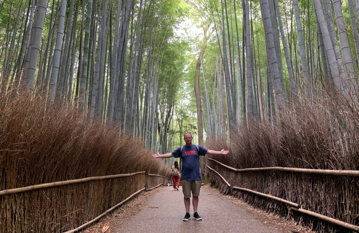 John Cross standing on trail in bamboo forest with outstretched arms.